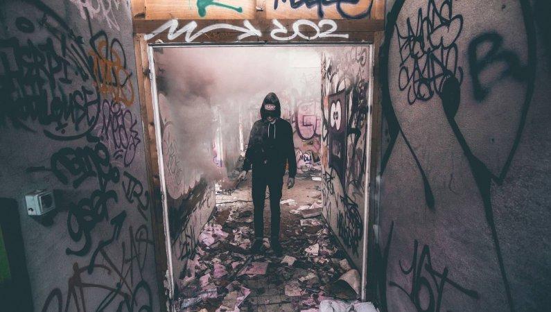 Abb. eines jungen Mannes mit tief ins Gesicht gezogenem Kaputzenpullover in einem verlassenen Wohnbau, in der linken Hand ein bengalisches Feuer.
