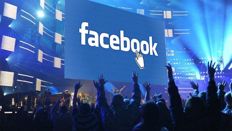 Blick zur Bühne eines Popkonzertes. Am Screen der Facebook-Schriftzug