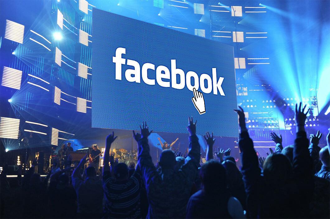 Facebook-Fanpages: Blick zur Bühne eines Popkonzertes; am Screen der Facebook-Schriftzug